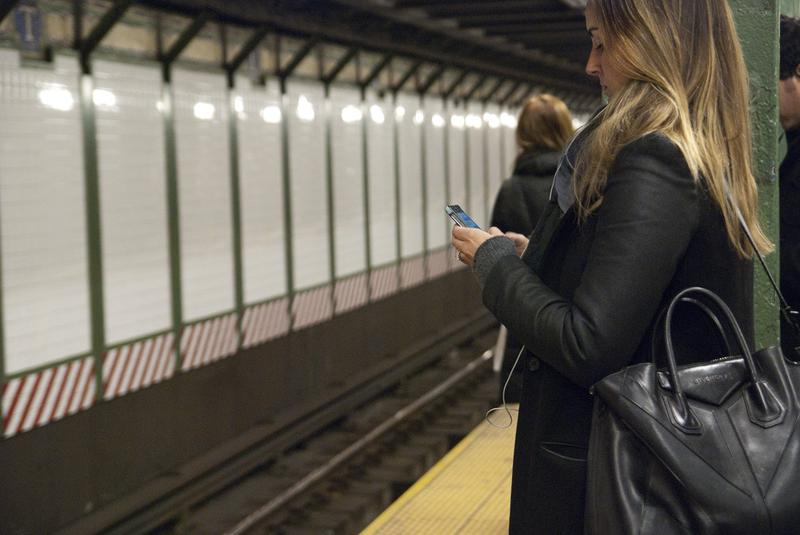 A woman uses her smartphone while waiting for the train in the Times Square subway station.