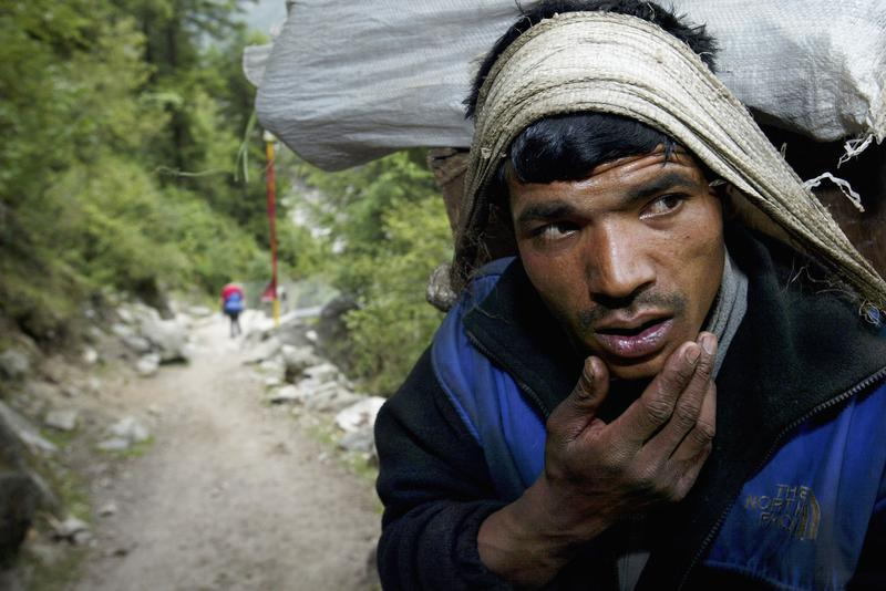 A Sherpa porter rests whist carrying a heavy load up the Everest trail May 25, 2003 in the Solu Khumbu region, Nepal.