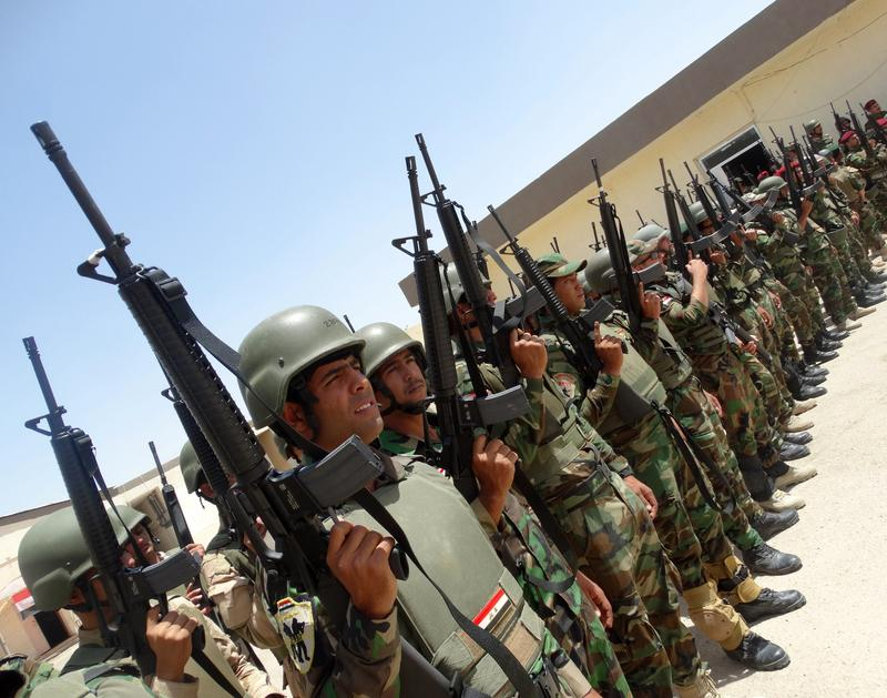 Iraqi troops stand in rows holding their weapons as they arrive to support the Sunni anti-Al-Qaeda militia Sahwa in its fight against anti-government militants.  June 21, 2014