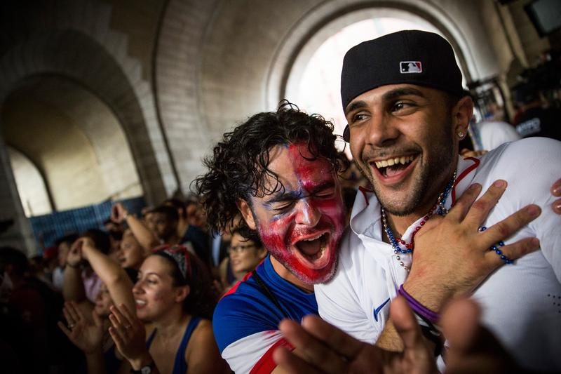 Christian Raja (L), of Brooklyn, reacts while watching the United States versus Belgium game in the World Cup on a projected screen under the Manhattan Bridge on July 1, 2014.