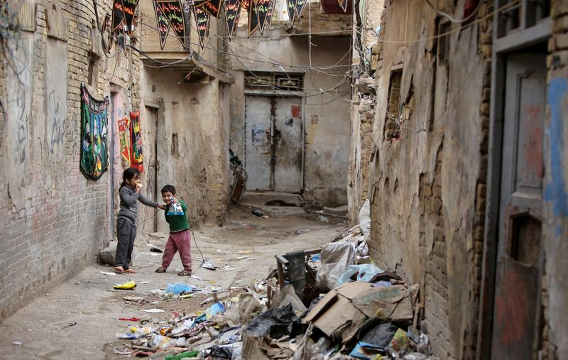Iraqi children stand in an alley in the old part of the capital Baghdad on December 13, 2013.