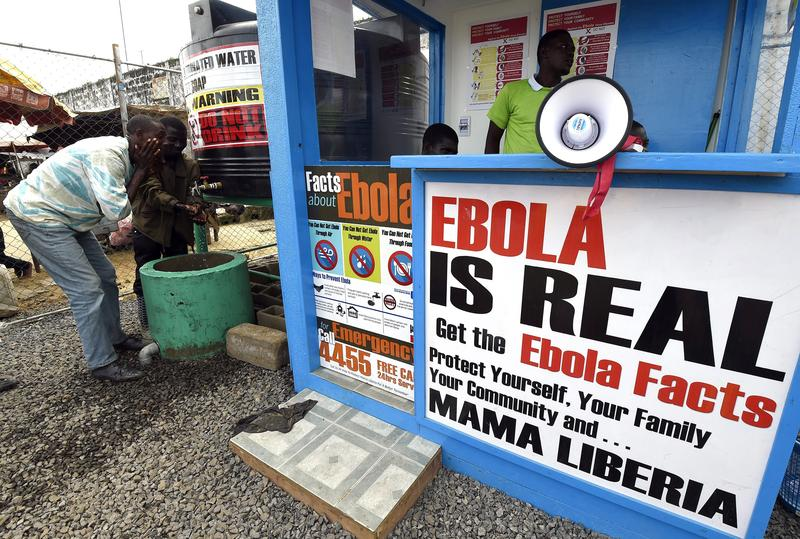 Liberians wash their hands next to an Ebola information and sanitation station raising awareness about the virus in Monrovia on September 30, 2014.