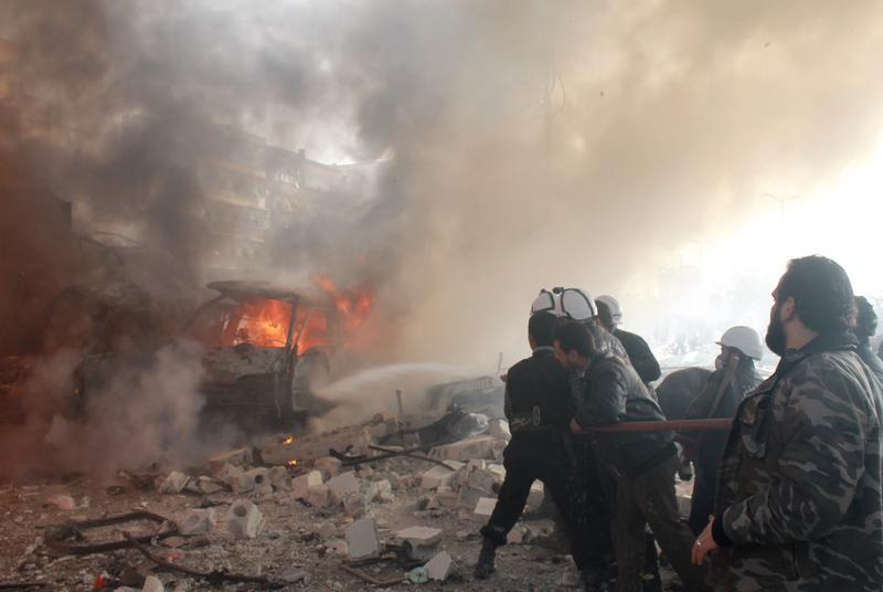 Syrian emergency personnel are seen exstinguishing a fire at the scene of a reported airstrike by government forces in the northern Syrian city of Aleppo on January 21, 2014.