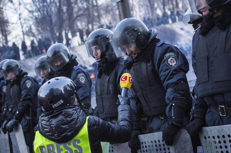 A Ukrainian policeman speaks to a journalist on Grushevskogo Street on January 27, 2013 in Kiev, Ukraine.