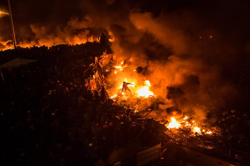 An anti-government protester stands amid burning tires to throw a Molotov cocktail toward police on Independence Square on February 19, 2014 in Kiev, Ukraine.