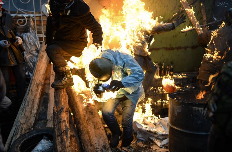 Protesters catch fire as they stand behind burning barricades during clashes with police on February 20, 2014 in Kiev.