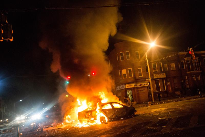 Two cars burn in the middle of an intersection at New Shiloh Baptist Church on April 27, 2015 in Baltimore, Maryland.