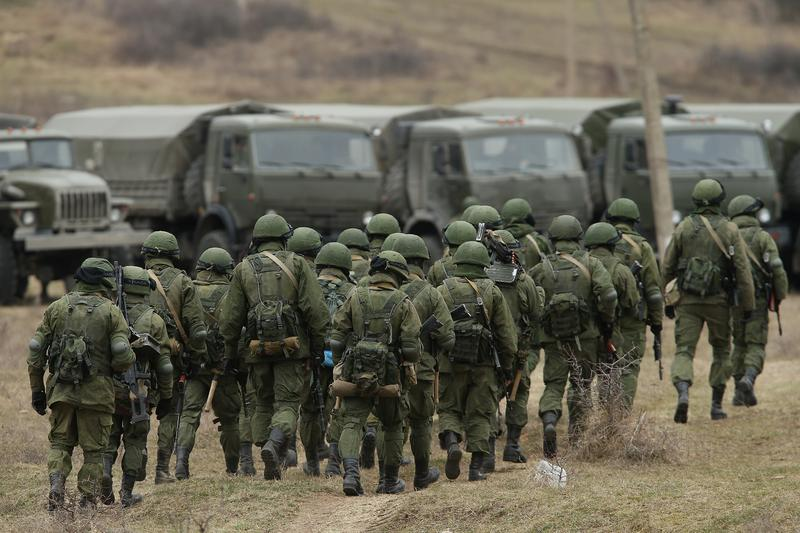Soldiers who were among several hundred that took up positions around a Ukrainian military base walk towards their parked vehicles in Crimea on March 2, 2014 in Perevalne, Ukraine.