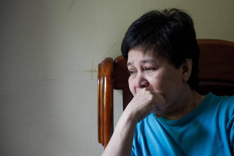 Sarah Nor, 55, the mother of 34-year-old Norliakmar Hamid, a passenger on a missing Malaysia Airlines Boeing 777-200 plane, talks on a mobile phone at her house in Kuala Lumpur on March 8, 2014.