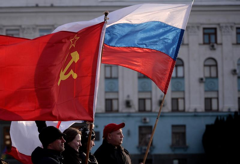 Men hold Russian (R) and Soviet Union flags in Simferopol's Lenin Square on March 16, 2014. Polls opened yesterday for a referendum on the peninsula of Crimea.