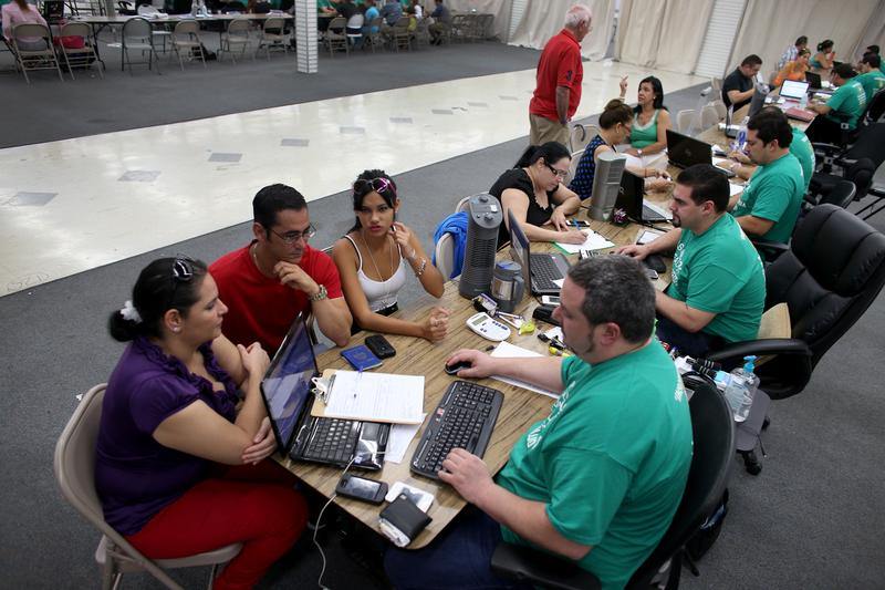 MARCH 20: (L-R) Yudelmy Cataneda, Javier Suarez & Claudia Suarez sit with Yosmay Valdivian, an insurance agent from Sunshine Life and Health Advisors as they & others try to purchase health insurance.