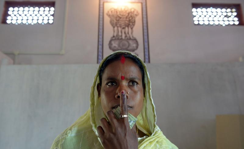 Indian resident Santoshi Bhumej, the first voter who entered the polling booth to cast her vote, poses after voting in Dibrugarh on April 7, 2014, during national elections.