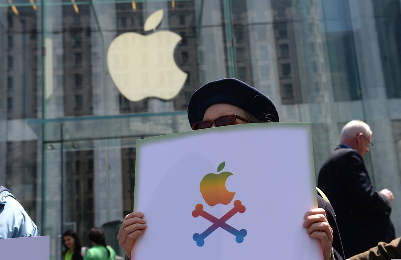 A demonstrator holds a sign against US computer and phone manufacturer Apple, in front of Apple's flagship store on Fifth Avenue in New York, April 25, 2014.
