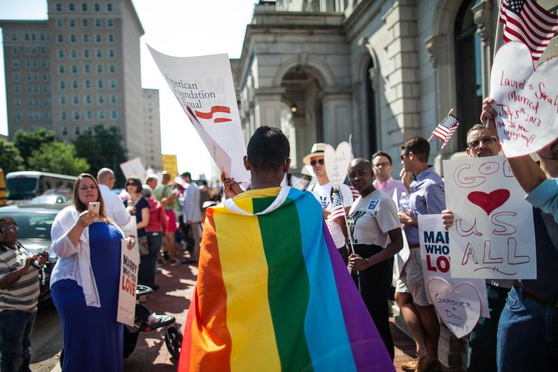 A same-sex marriage supporter wears a rainbow cape behind 4th U.S. Circuit Court of Appeals after a court hearing May 13, 2014 in Richmond, Virginia.