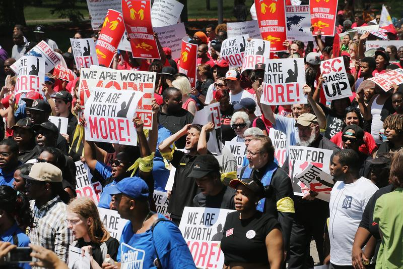 Fast food workers and activists demonstrate outside the McDonald's corporate campus on May 21, 2014 in Oak Brook, IL. Demonstrators were calling on McDonald's to pay a minimum wage of $15-per hour.
