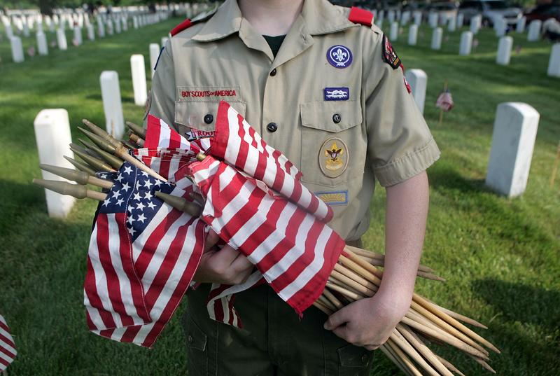A Boy Scout holds flags that are going to be placed on each grave at Zachary Taylor National Cemetery May 26, 2007 in Louisville, Kentucky.