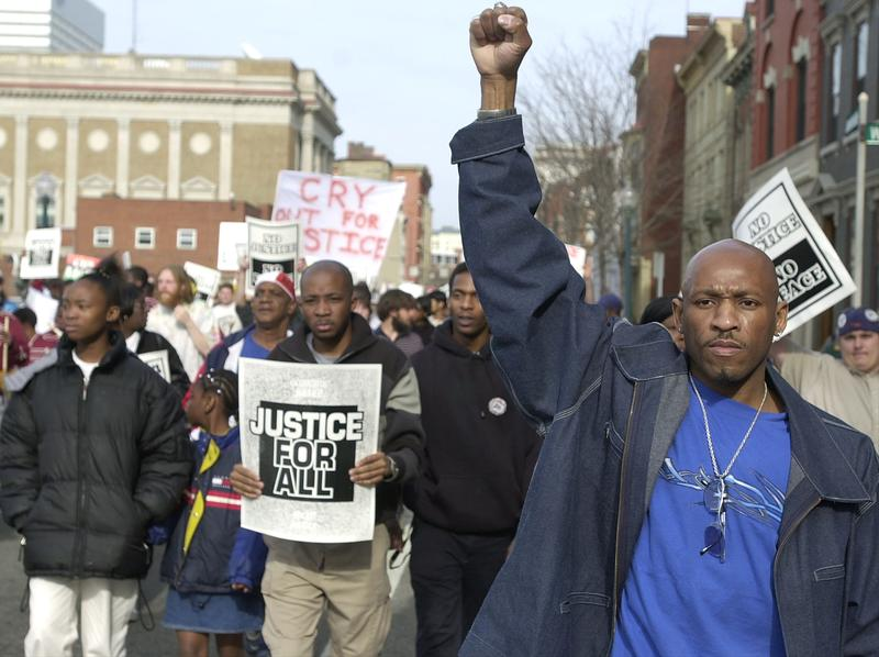 Protesters participate in a March for Justice April 7, 2002 in Cincinnati, OH. The march was held to mark the one year anniversary police shooting death of Timothy Thomas.