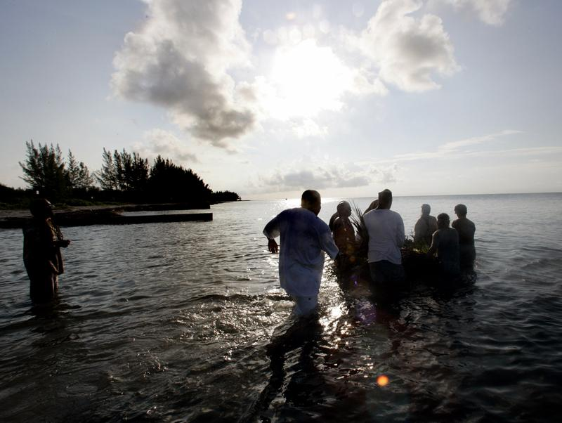 Jun 19, 2005: A group of men wade into the ocean during a sunrise ceremony to mark Juneteenth.