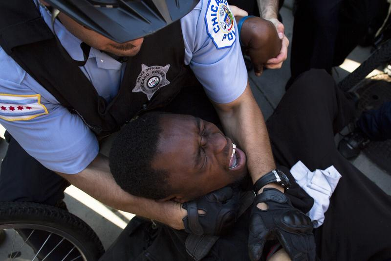 A NATO protestor is arrested after refusing to let go of a police bicycle, Saturday, May 19, 2012, in Chicago.
