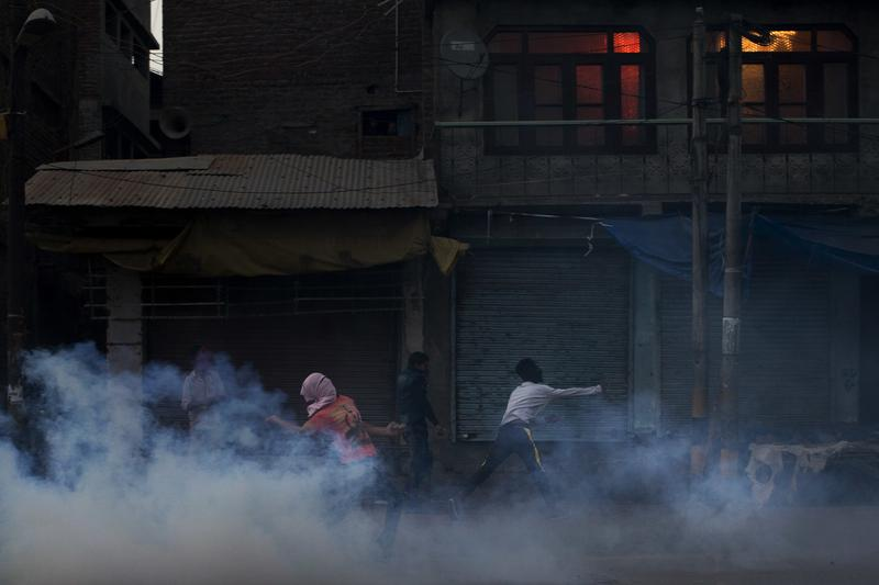 Sept. 29, 2016: Kashmiri protesters prepare to throw exploded tear gas shell back at Indian police men.