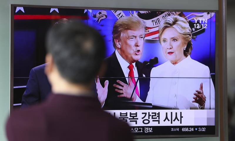 A man watches a TV screen showing the presidential debate between Hillary Clinton and Donald Trump in Seoul, South Korea. October 20, 2016
