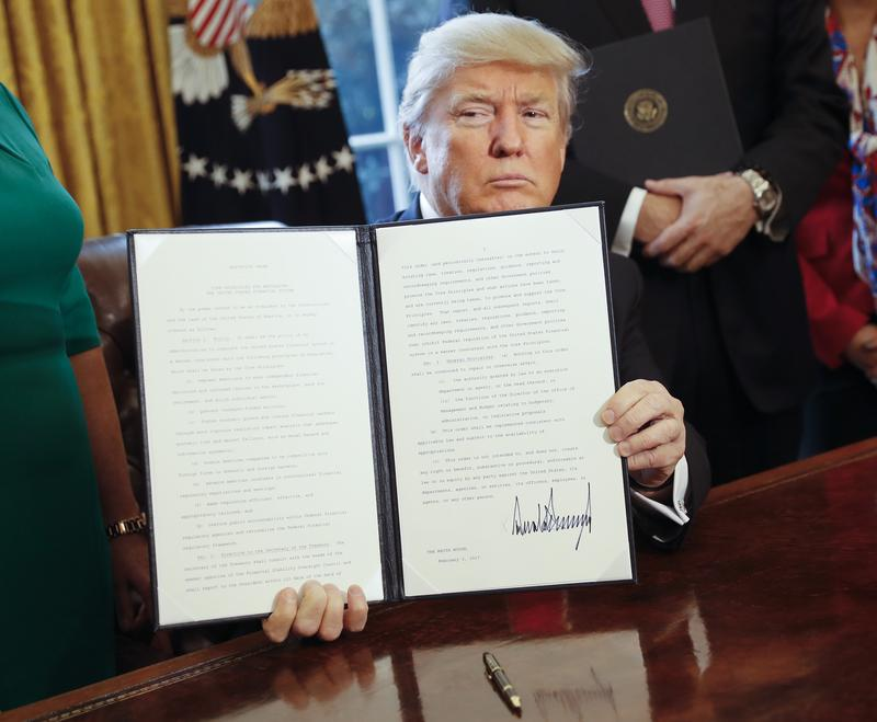 President Donald Trump holds up an executive order after his signing the order in the Oval Office of the White House in Washington, Friday, Feb. 3, 2017.