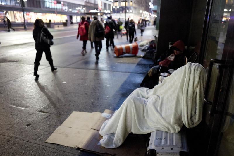 A homeless person sleeps under a blanket on a New York sidewalk