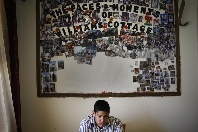 April 24, 2014: Angel B., 15, sits under a board displaying past and present residents of Williams Cottage group foster home at the Children's Village campus in Dobbs Ferry, N.Y.