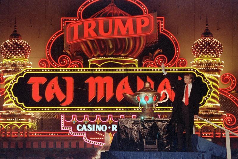 In this April 5, 1990 file photo, Donald Trump stands next to a genie lamp of his Trump Taj Mahal Casino Resort in Atlantic City, N.J.