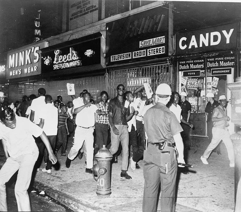During the Harlem Riots of 1964, protesters march down 125th street with photographs of Lieutenant Thomas Gilligan.