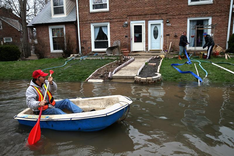 Octavio Castillo paddles a boat down a flooded street to reach the home of his cousin on April 19, 2013 in Des Plaines, Illinois, a suburb of Chicago.