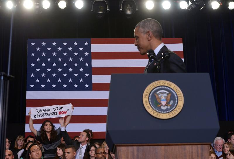 A protestor holds up a banner as a guest beside her reaches to pull it away as US President Barack Obama speaks on immigration reform at the Copernicus Community Center on November 25, 2014 in Chicago