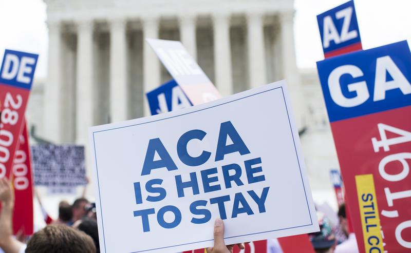 Affordable Care Act supporters wave signs outside the Supreme Court after the court upheld court's Obamacare on Thursday, June 25, 2015.