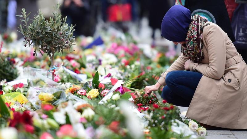 A Muslim woman lights a candle at a makeshift memorial for the victims of the terrorist attacks in France, in front of the French embassy in Berlin on November 16, 2015.