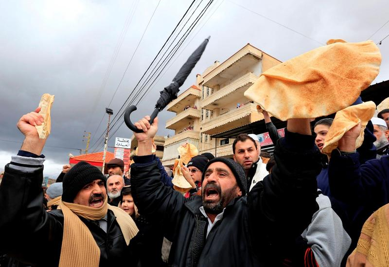 Protesters on the Syrian-Lebanon border hold bread to raise awareness of the situation in Madaya.