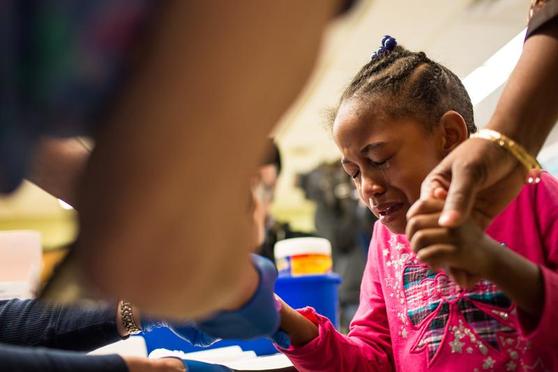 Tears stream down the face of Morgan Walker, age 5 of Flint, as she gets her finger pricked for a lead screening on January 26, 2016 at Eisenhower Elementary School in Flint, Michigan.