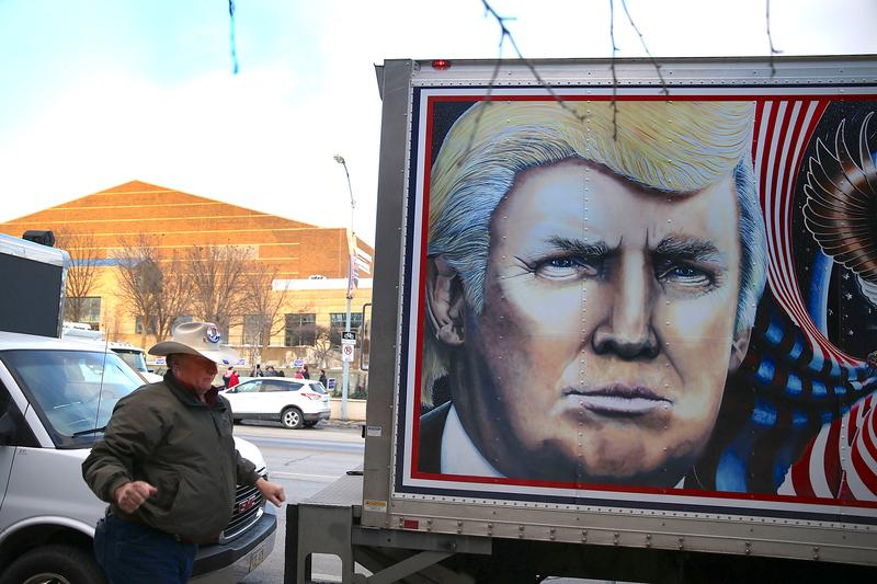 Kraig Moss helps park a truck with a painting of Republican Presidential candidate Donald Trump on it outside the Iowa Events Center where the Republican debate is taking place on January 28, 2016.