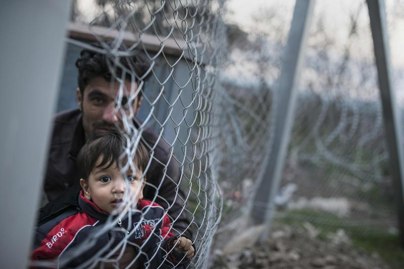 A photo taken from the Macedonian side of the border shows an Afghan man sitting with a young boy behind a fence at the Greek-Macedonian border, near Gevgelija. Feb. 22, 2016