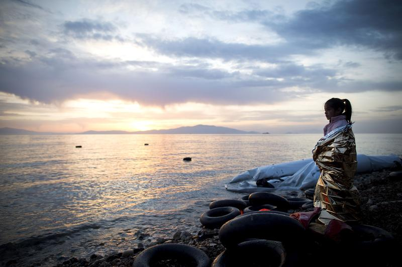 A small Syrian girl looks on during sunrise after arriving on an inflatable boat with other refugees on March 9, 2016 in Mytelene, Greece.