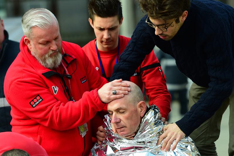A victim receives first aid by rescuers, on March 22, 2016 near Maalbeek metro station in Brussels, after a blast at this station near the EU institutions caused deaths and injuries.