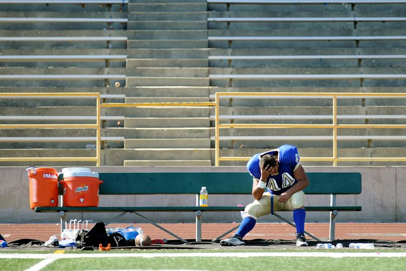 Calvary Babtist High School football player Raymond Zambrano sits on the bench after injuring his knee against Lee Vining High School during a game at Damien High in La Verne.