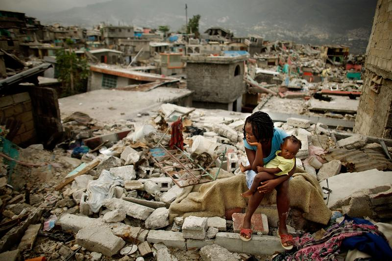 PORT-AU-PRINCE, HAITI - FEBRUARY 26, 2010: Sherider Anilus, 28, and her daughter, 9-month-old Monica, sits on the spot where her home collapsed during the 2010 earthquake in Haiti.