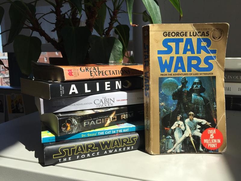 Copies of the novelizations of Star Wars, Great Expectations, Alien, The Cabin in the Woods, Pacific Rim, The Cat in the Hat, and Star Wars: The Force Awakens.