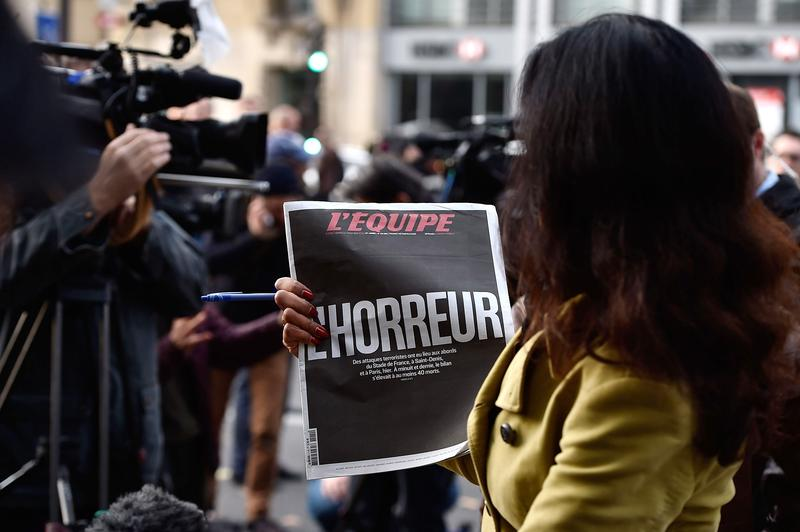 A Sky News journalist holds a French newspaper after a terrorist attack on November 14, 2015 in Paris, France.