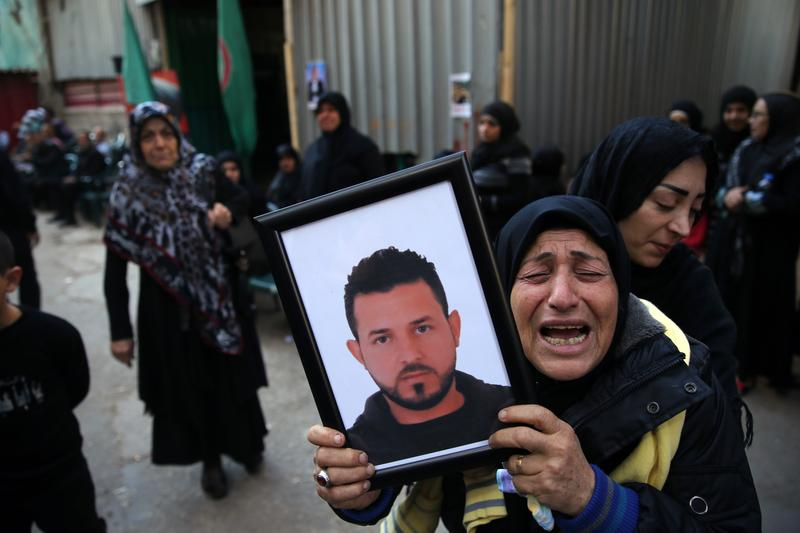 A relative of Samer Huhu, who was killed in a twin bombing attack that rocked a busy shopping street in the area of Burj al-Barajneh in southern Beirut, mourns him during his funeral.