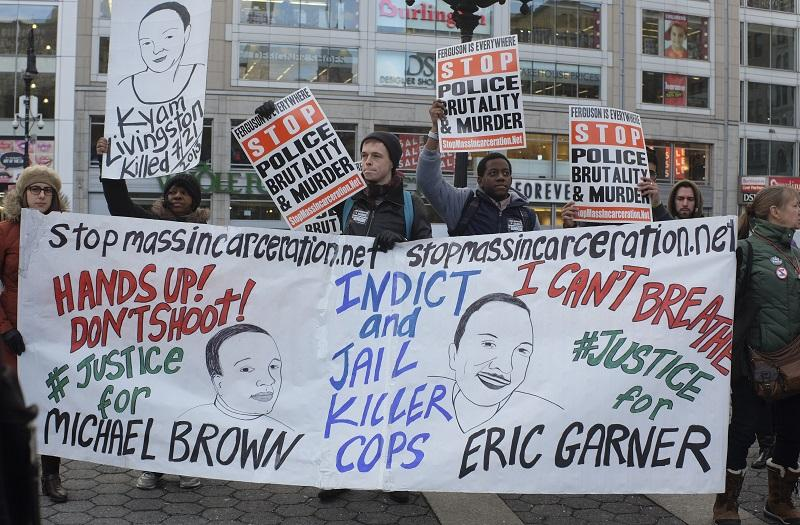 NEW YORK CITY - JANUARY 19 2015: several hundred activists gathered at Union Square Park prior to starting the Four Mile March on Martin Luther King's birthday. Eric Garner, Michael Brown banner