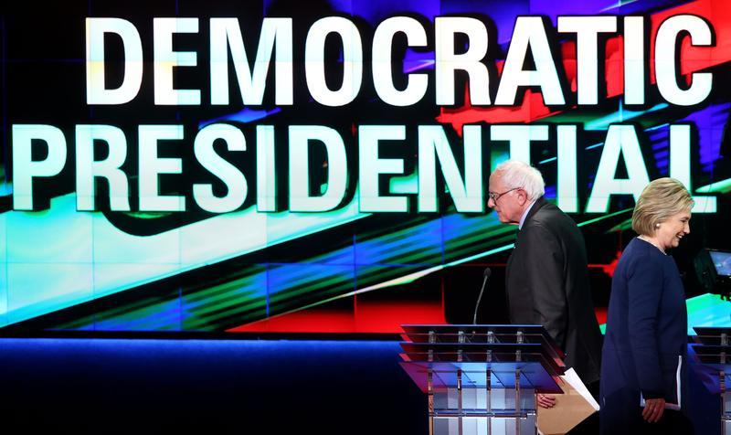 Democratic presidential candidates Senator Bernie Sanders (D-VT) and Hillary Clinton walk off stage during a break in the CNN Democratic Presidential Primary Debate in Flint, Michigan.