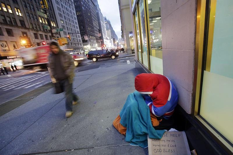A homeless person sleeps on a New York sidewalk, Wednesday morning, Jan. 14, 2015. The overnight temperature was 17 degrees (- 8C).