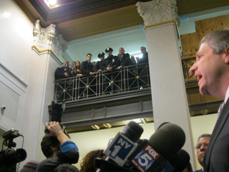 NYPD police officers watch and listen as Pat Lynch addresses the media in the court house.