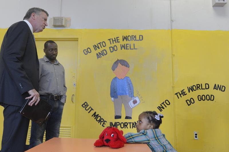 Mayor Bill de Blasio with the father of a young girl who received a placement in a public school pre-k program.